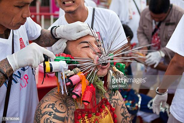 Thai man getting his cheeks pierced at Vegetarian festival in Phuket, Thailand. During the performances of religious rites at the temples, the...