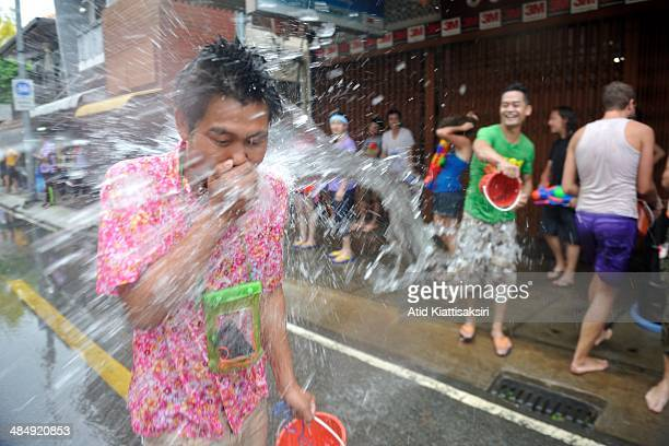 Thai man is splashed with water during the Songkran festival on Tapae street The Songkran festival which is the traditional Thai new year is...