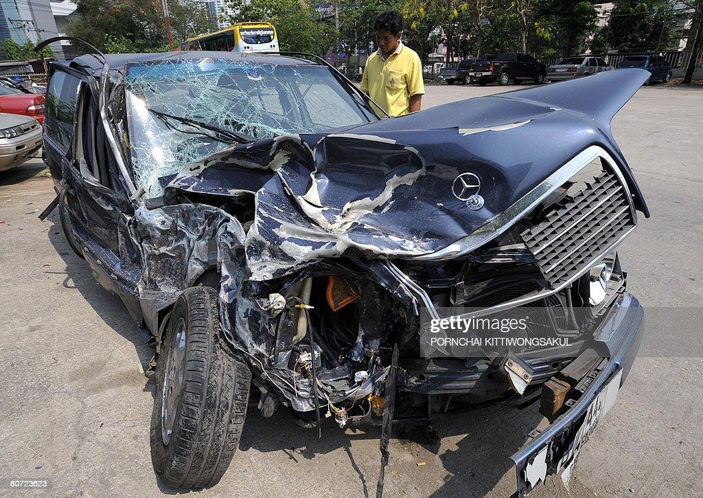 A Thai man looks at a car wrecked in a r : Nachrichtenfoto