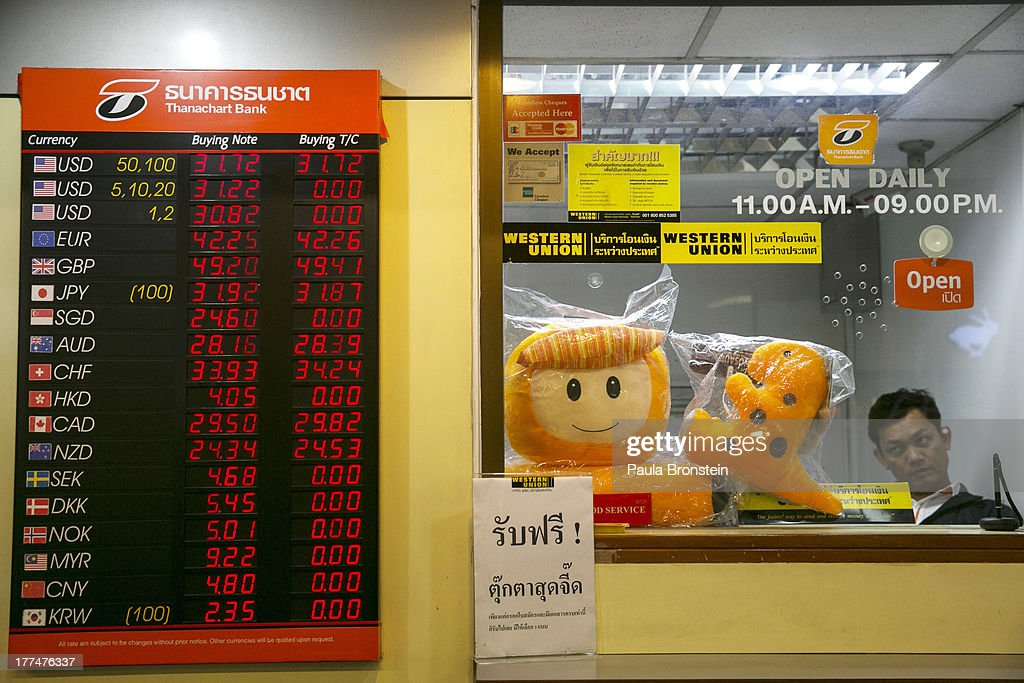 A Thai man looks out from a money exchange bank kiosk on August 23, 2013 in downtown Bangkok, Thailand. The local currency dropped to its lowest level since August 2010. Against the US dollar the Thai baht fell to 32.09/32.13 dropping about 5% this year.