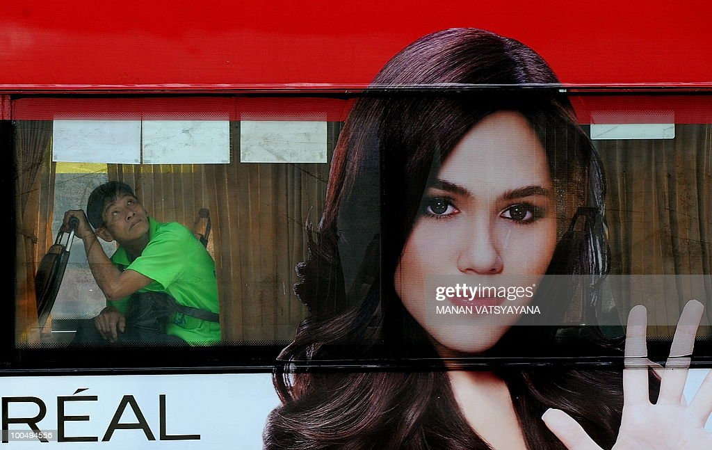 A Thai man peeks out of a bus in Bangkok on May 25, 2010. Thai authorities will ask the government to extend a curfew in Bangkok and 23 provinces for another week in the wake of a crackdown on anti-government protesters, an army official said.