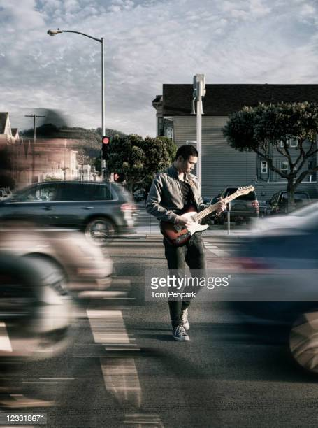 thai man playing guitar in crosswalk - oblivious stock pictures, royalty-free photos & images
