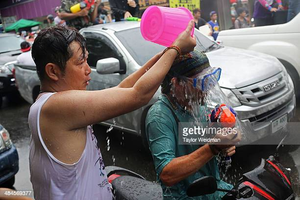 Thai man pours a bucket of water on a foreigner riding a scooter during Songkran on April 13 2014 in Chiang Mai Thailand Songkran is the traditional...