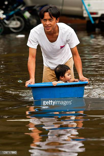 A Thai man pushes a bucket with a child inside through floodwaters in the inundated district of Rangsit northern Bangkok on October 20 2011...