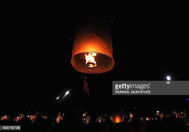 A Thai man releases a paper lantern during a function to celebrate the 86th birthday of King Bhumibol Adulyadej light up the night sky in Bangkok on...