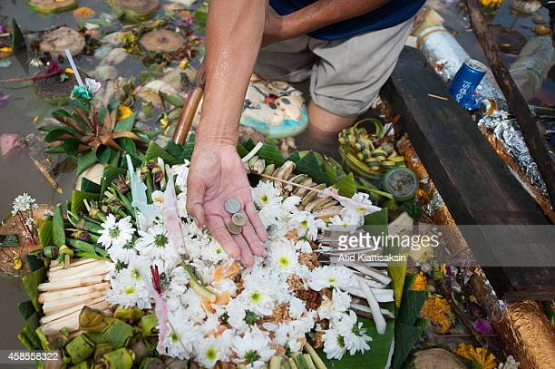 Thai man shows some Thai Baht coins that he found on a krathong that was floating on the Ping river during Loy Krathong Festival in Chiang Mai....