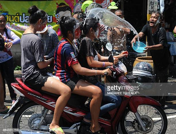 Thai man splashes water on motorist during celebrations of Songkran the water festival marking the country's new year in Thailand's southern province...