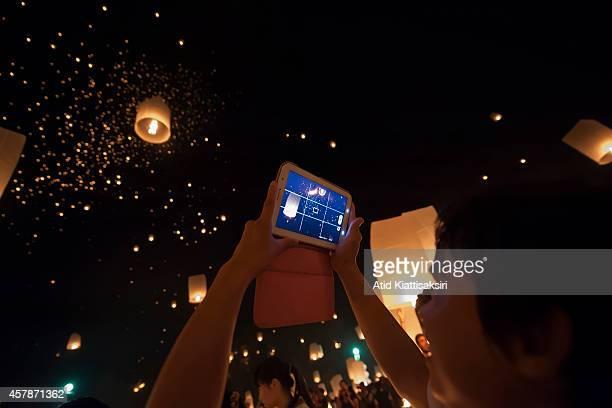Thai man using his tablet records thousands of Khom Lois during the Yi Peng Festival at Lanna Dhutanka
