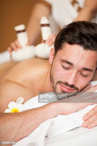 thai massage of a man's back - thai massage stock photos and pictures