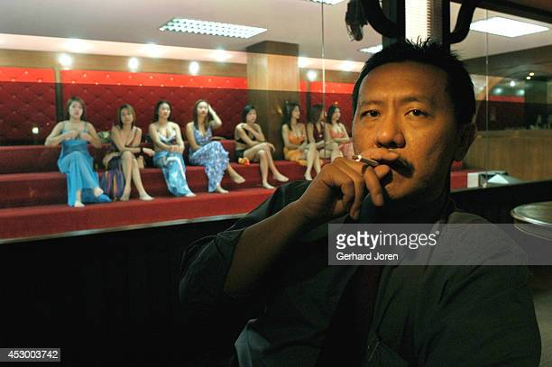 Thai 'massage' tycoon Chuwit Kamolvisit sits in the foyer of one of his massage parlours while Thai masseuses wait for customers at the Copacabana...