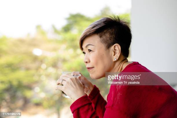 thai mature woman enjoys her morning with a cup of coffee - showus stock pictures, royalty-free photos & images