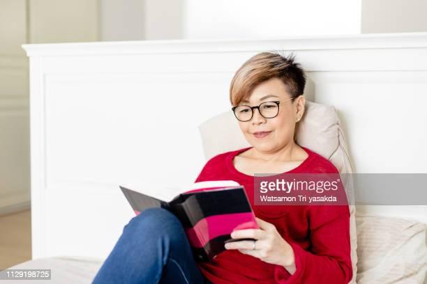 thai mature woman enjoys reading a book - タイ人 ストックフォトと画像