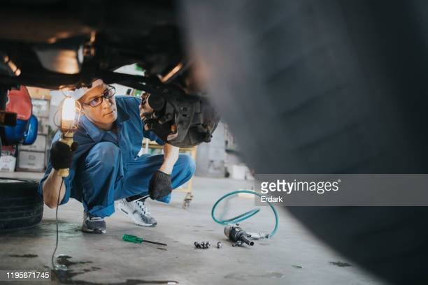 thai mechanic man with lamp working at car auto repair  shop stock photo - suspension bridge stock pictures, royalty-free photos & images