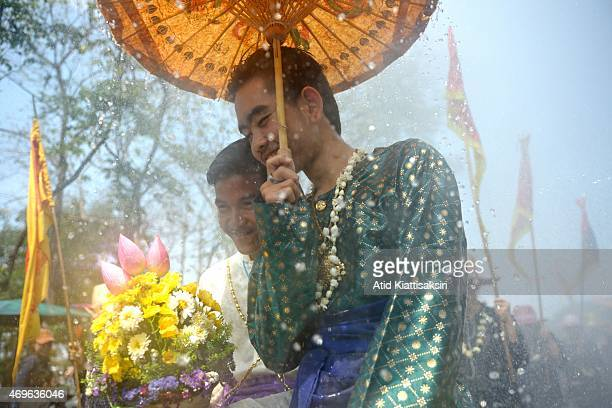 Thai men dressed in traditional costumes using an umbrella to protect themselves from water splashes as they walk in a procession during the Songkran...