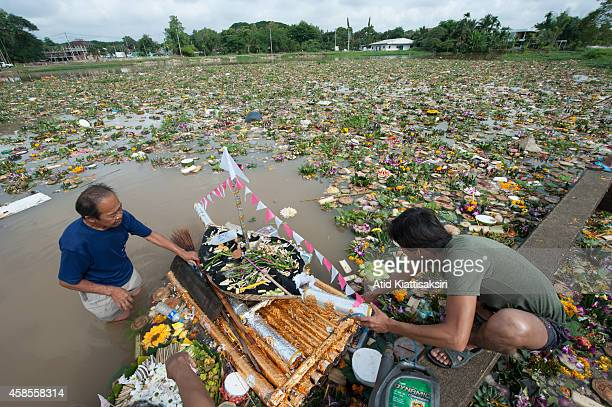 Thai men find valuables from a big krathong on the Ping river during Loy Krathong Festival in Chiang Mai. People place money along with candles and...