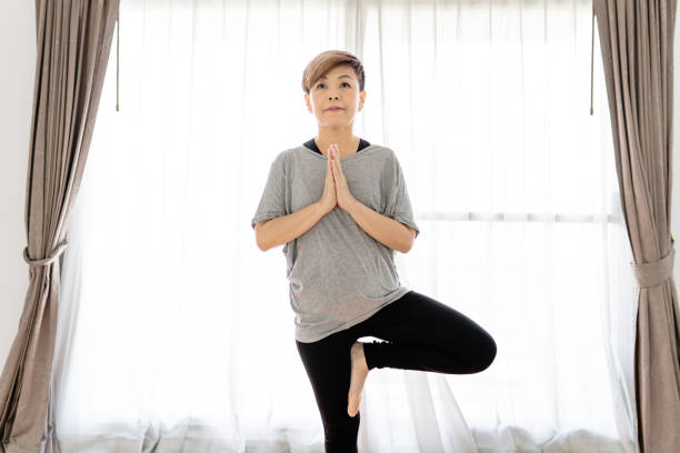 Thai middle-aged woman enjoys yoga at home
