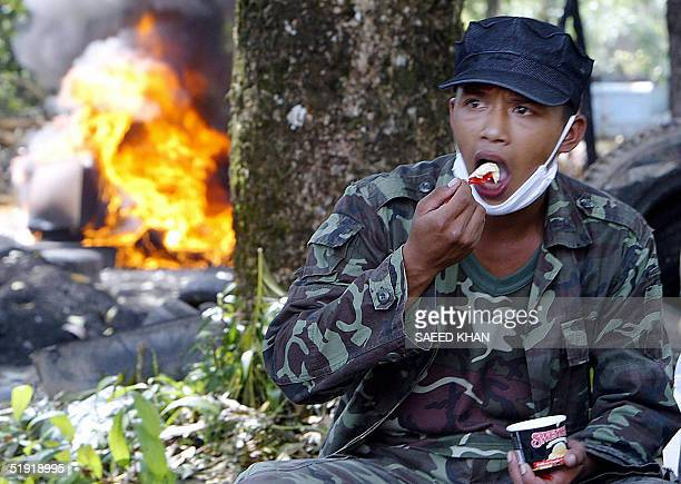 Thai military rescuer eats ice cream while sitting next to a burning coffin of a tsunami disaster victim at the cremation site of Bang Mak Roang...