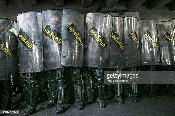 BANGKOK THAILAND MAY 25 Thai military stand behind their riot shields as protesters threaten them during an anticoup protest on the third day of the...
