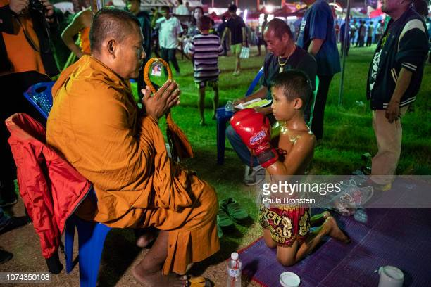 Thai monk offers a blessing to a young fighter before he fights during a Muay Thai boxing competition on December 7 2018 in Lopburi Thailand A...