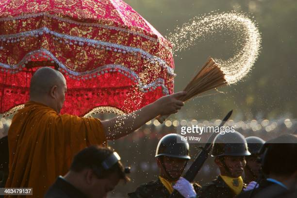 Thai monk sprays water on parading soldiers as a blessing during a celebration of Thai Armed Forces Day at a military barracks on January 18 2014 in...