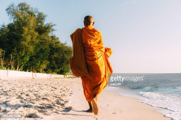 monaco tailandese che cammina sulla spiaggia in thailandia - monaco foto e immagini stock