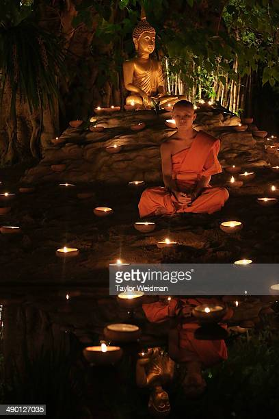 Thai monks at Wat Pan Tao take part in a candle lighting ceremony celebrating Visak Day on May 13 2014 in Chiang Mai Thailand Visak Day is a...
