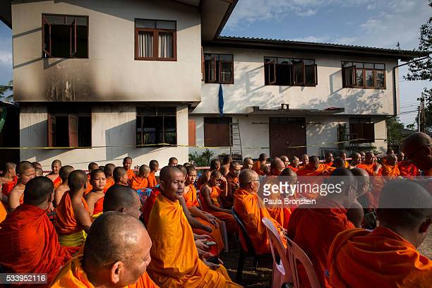 Thai monks gather outside the school dormitory for a prayer where a fire broke out on Sunday night killing at least 17 girls in Wiang Papao Chiang...