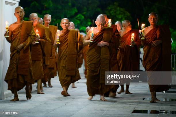 Thai monks hold candles and incense they perform during a ceremony marking Asalha Puja Day in Wat Asokaram Samut Prakan Thailand 8 July 2017 Asalha...