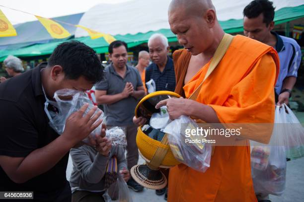 Thai monks of Dhammakaya Temple collect morning alms from worshipers outside Wat Phra Dhammakaya Temple in Pathum Thani. Thai authorities plan to...