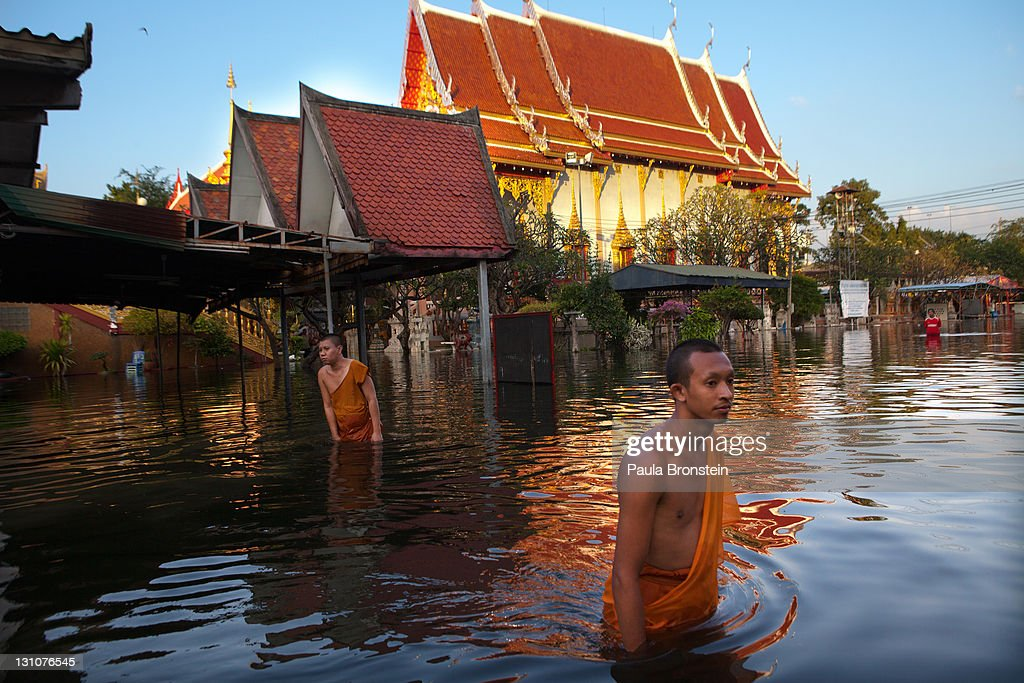Thai monks wade through the dirty waters at the flooded Laksi temple November 1, 2011 in Bangkok, Thailand. Thousands of flood victims have been forced to take shelter at crowded evacuation centers around the capitol city. Hundreds of factories have been closed in the central Thai province of Ayutthaya and Nonthaburi. Thailand is experiencing the worst flooding in over 50 years which has affected more than nine million people. Over 400 people have died in flood-related incidents since late July according to the Department of Disaster Prevention and Mitigation.