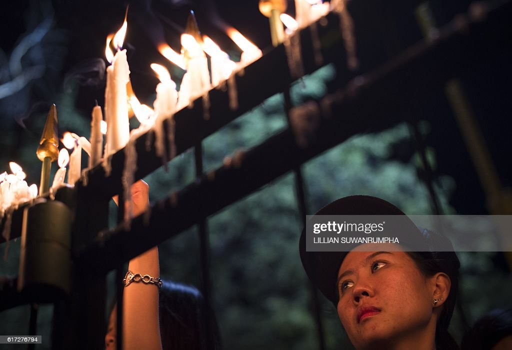 A Thai mourner clad in black lights candles for late Thai King Bhumibol Adulyadej at the Sanam Luang Park outside the Grand Palace in Bangkok on October 22, 2016. Thailand's King Bhumibol Adulyadej died at the age of 88 on October 13 after years of ill health, ending a seven-decade reign and leaving the politically divided nation without its key pillar of unity. / AFP / LILLIAN