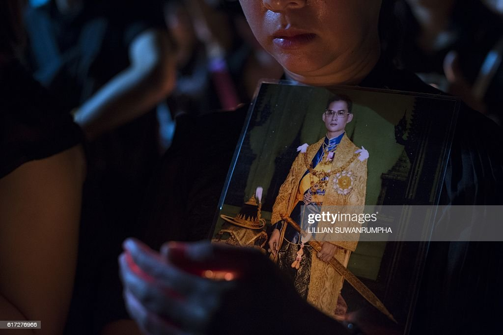 A Thai mourner clad in black lights holds a picture of late Thai King Bhumibol Adulyadej at the Sanam Luang Park outside the Grand Palace in Bangkok on October 22, 2016. Thailand's King Bhumibol Adulyadej died at the age of 88 on October 13 after years of ill health, ending a seven-decade reign and leaving the politically divided nation without its key pillar of unity. / AFP / LILLIAN