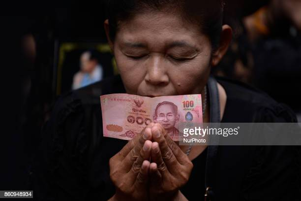 Thai mourner hold Thai baht the portrait of King Bhumibol Adulyadej at Siriraj Hospital where he died in Bangkok, Thailand, Friday, 13 October 2017....