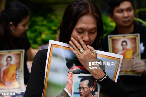 Thai mourner holds a portrait of the late Thai King Bhumibol Adulyadej at Siriraj Hospital where he died in Bangkok, Thailand, Friday, 13 October...