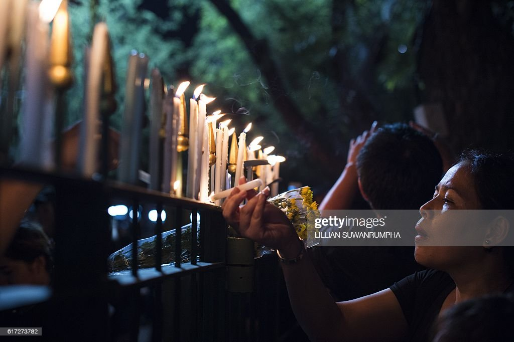 Thai mourners clad in black light candles for late Thai King Bhumibol Adulyadej at the Sanam Luang Park outside the Grand Palace in Bangkok on October 22, 2016. Thailand's King Bhumibol Adulyadej died at the age of 88 on October 13 after years of ill health, ending a seven-decade reign and leaving the politically divided nation without its key pillar of unity. / AFP / LILLIAN