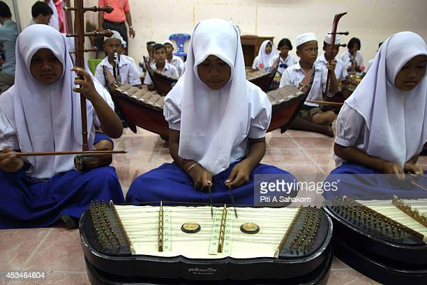 Thai Muslim and Buddhist students learning traditional Thai music at Ban Muang Ngam school in Songkhla province a school which offers both Islamic...