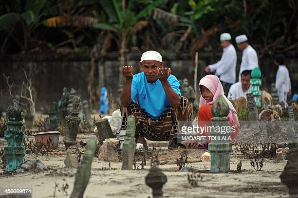 A Thai Muslim man prays at a cemetery during the sacrificial Eid alAdha festival in the southern province of Narathiwat on October 5 2014 The...
