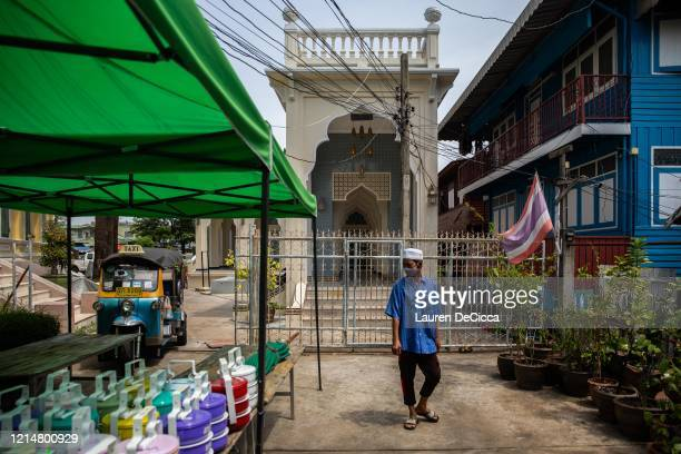 Thai Muslim man walks past tiffen boxes containing food donations at the Bang Ao Mosque on the last day of Ramadan on May 23 2020 in Bangkok Thailand...