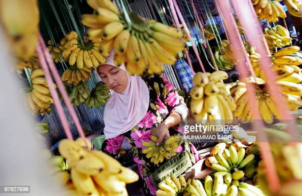 A Thai Muslim woman arranges bananas at her market stall in the southern province of Yala on March 3 2010 Thailand's inflation rose for the fifth...