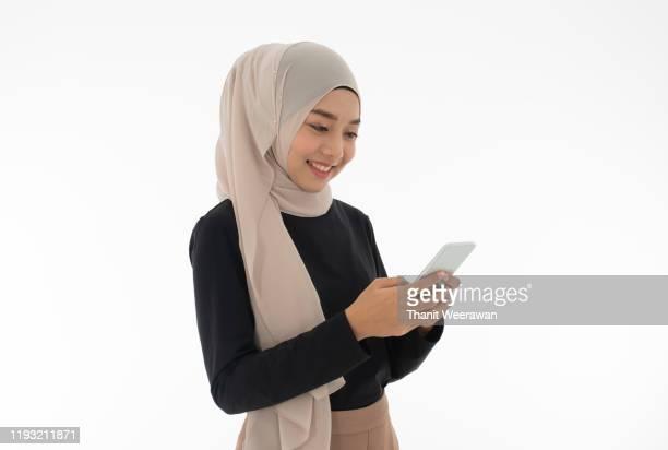 thai muslim woman in woman muslim dress (hijab) enjoying playing mobile phoneon white background. - 宗教的なベール ストックフォトと画像