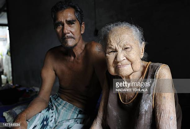Thai Muslim woman Tuweasong Tuweanok 103yearold poses for pictures with her son at her home in Thailand' southern province of Narathiwat on April 10...