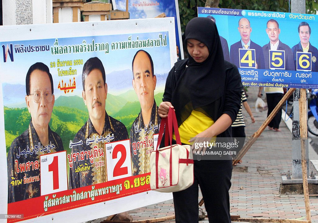 A Thai Muslim woman walks past election : News Photo