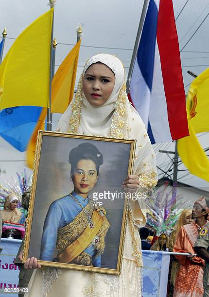 A Thai Muslim woman while holding a portrait of Thai Queen Sirikit marches in a rally organised in connection with the birthday ceremonies of the...