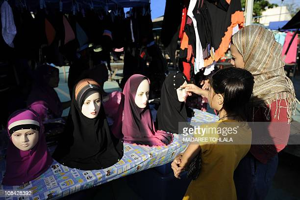 Thai Muslim women select clothes at a market place in Narathiwat southern Thailand on January 22 2011 The Thai economy remained relatively resilient...