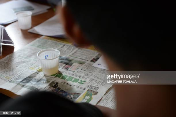 A Thai Muslim youth submits urine sample for drug testing in Bacho district in Thailand's southern province of Narathiwat on November 15 2018 during...