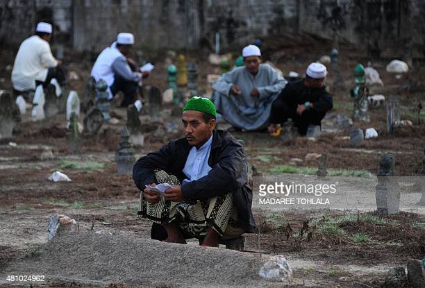 Thai Muslims pray at a cemetery on the first day of Eid alFitr celebrations in Thailand's southern province of Narathiwat on July 17 2015 Muslims...