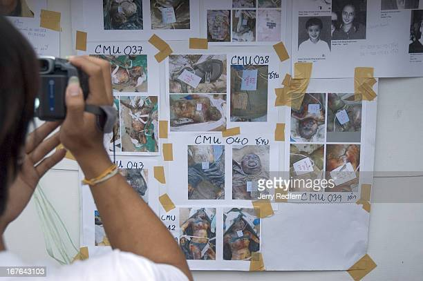 Thai national videotapes photos of victims and missing people at the missing persons information center at Khao Lak nearly a week after the December...