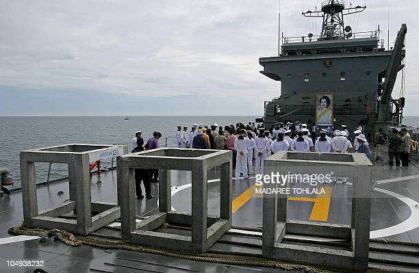 Thai navy and department of fishery officials stand in front of a portrait of Thai Queen Sirikit before dumping cement platforms into the sea on a...