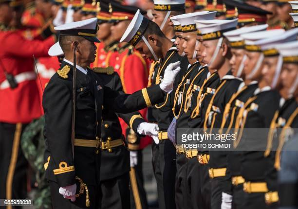 Thai officer makes adjustments to the uniforms of Thai naval cadets in formation at the presidential palace in Bangkok ahead of the arrival to the...