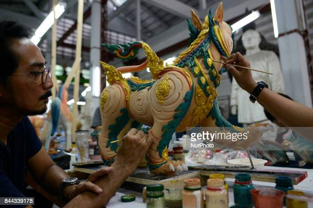 Thai official painters work on a deity sculpture which will be used to decorate the royal crematorium for the late Thai King Bhumibol Adulyadej's...